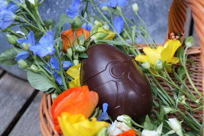 Œuf de Pâques Cavaletti sur un panier rempli de fleurs