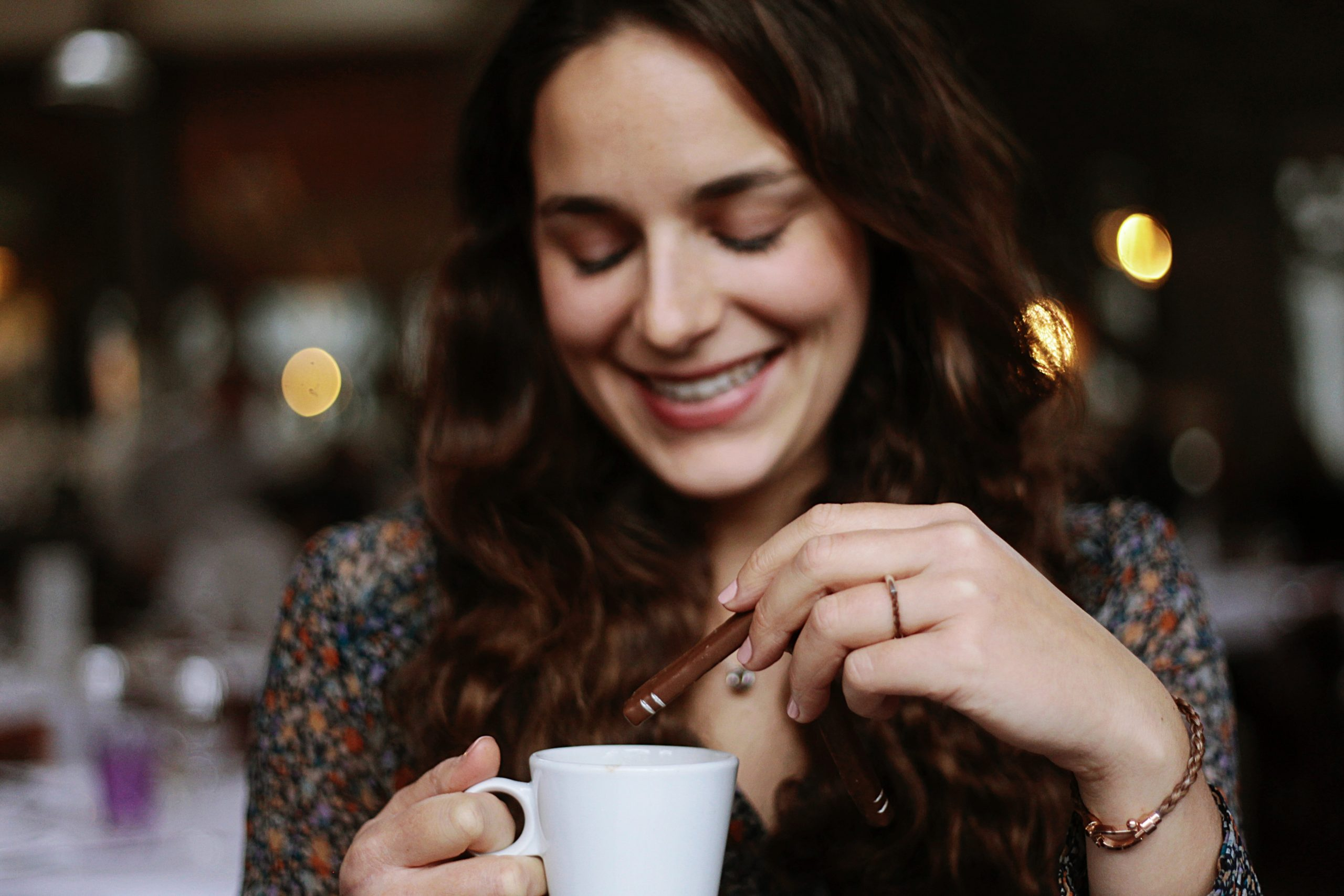 happy woman dipping Cavaletti chocolate praliné in coffee